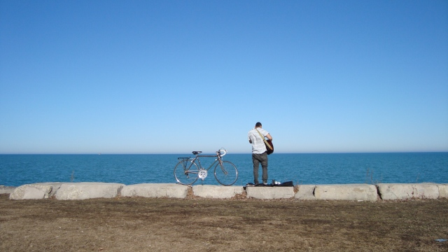 A lone guitarist playing to lake Michigan