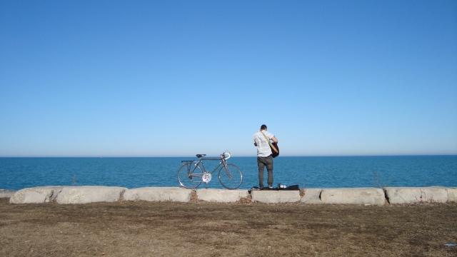 A lone guitarist playing to lake Michigan